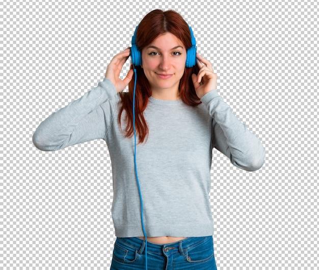 Junges rothaarigemädchen, das musik mit kopfhörern hört