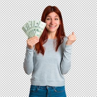 Junges rothaarigemädchen glücklich, weil eine menge geld gewonnen hat