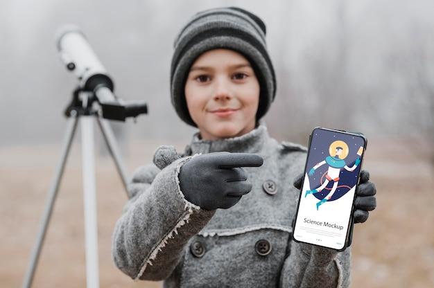 Kind, das wissenschaft lernt, während es ein smartphone-modell hält