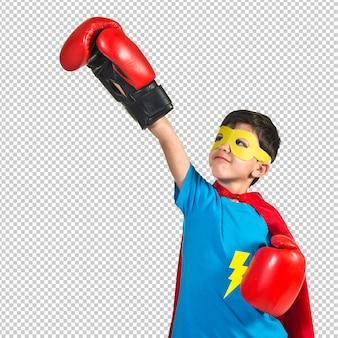 Kind gekleidet wie superheld mit boxhandschuhen
