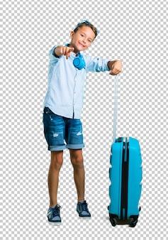Kind mit sonnenbrille und kopfhörer, die mit seinem koffer reisen, zeigt mit dem finger auf sie