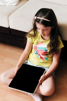 Kind sitzt auf einem boden mit einem digitalen tablett in ihren händen