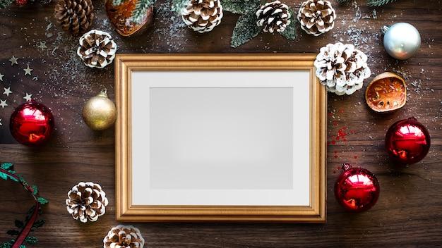Klassisches goldrahmenmodell mit weihnachtsdekorationen auf hölzernem hintergrund