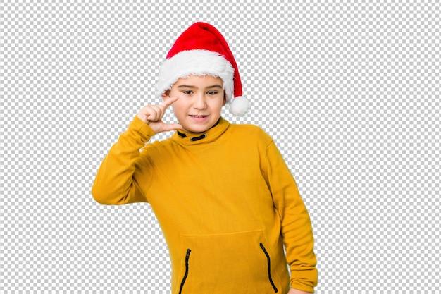 Kleiner junge, der den weihnachtstag trägt einen sankt-hut hält etwas klein mit den zeigefingern feiert, lächelt und überzeugt.