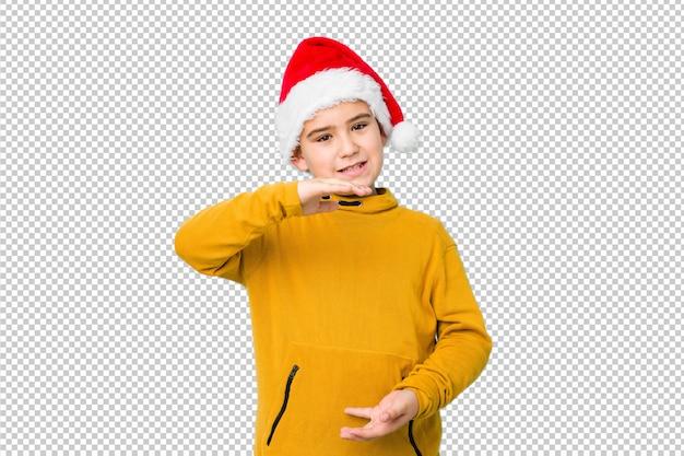 Kleiner junge, der den weihnachtstag trägt einen sankt-hut hält etwas mit beiden händen, produktdarstellung feiert.