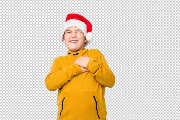 Kleiner junge, der den weihnachtstag trägt einen sankt-hut lacht feiert, hände auf herzen, konzept des glückes halten.