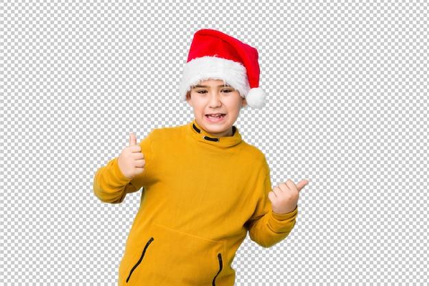 Kleiner junge, der den weihnachtstag trägt einen sankt-hut oben anhebt beide daumen, lächelt und überzeugt feiert.