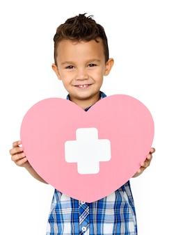 Kleiner junge, der ein symbol der medizinischen behandlung lächelt und hält