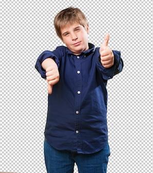 Kleiner junge, der ein widersprüchliches symbol tut