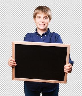 Kleiner junge, der eine tafel anhält