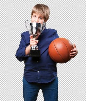 Kleiner junge, der einen bascketballwettbewerb gewinnt