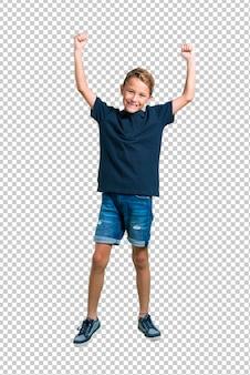 Kleiner junge, der einen sieg feiert