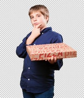 Kleiner junge, der pizzakästen hält