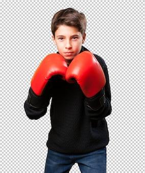 Kleiner junge, der rote boxhandschuhe trägt