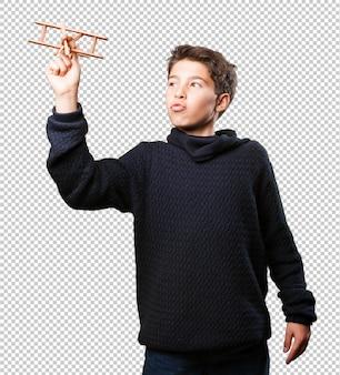 Kleiner junge mit einem hölzernen flugzeug auf weiß
