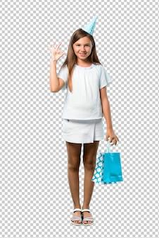 Kleines mädchen an einer geburtstagsfeier, die eine geschenktasche zeigt ein okayzeichen mit den fingern hält