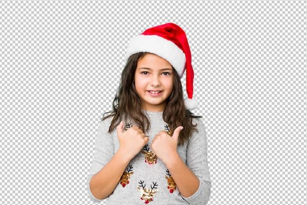 Kleines mädchen, das den weihnachtstag oben anhebt beide daumen, lächelt und überzeugt feiert.