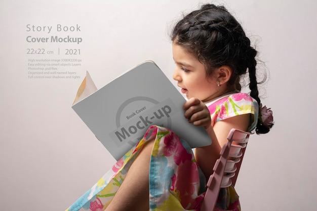 Kleines mädchen, das ein geschichtenbuch mit leerem einband liest