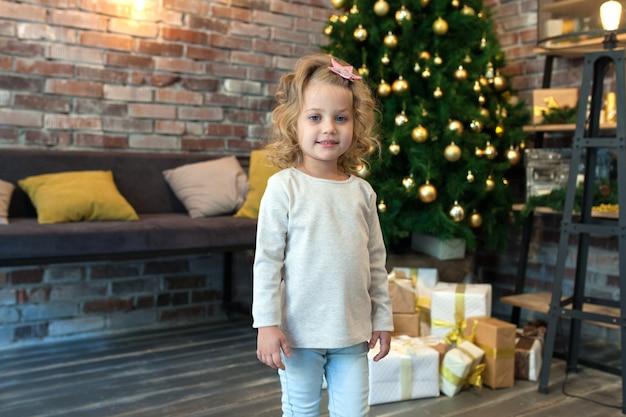 Kleines mädchen neben dem weihnachtsbaum, mit modellpullover für ihr design