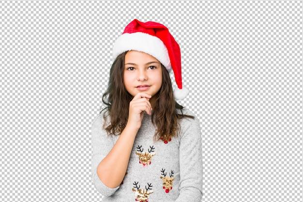 Kleines mädchen, welches das weihnachtstaglächeln glücklich und überzeugt, rührendes kinn mit der hand feiert.