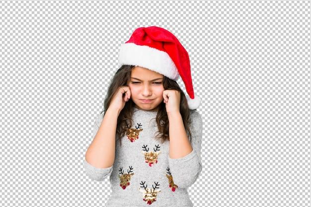 Kleines mädchen, welches den weihnachtstag bedeckt ohren mit den händen feiert.