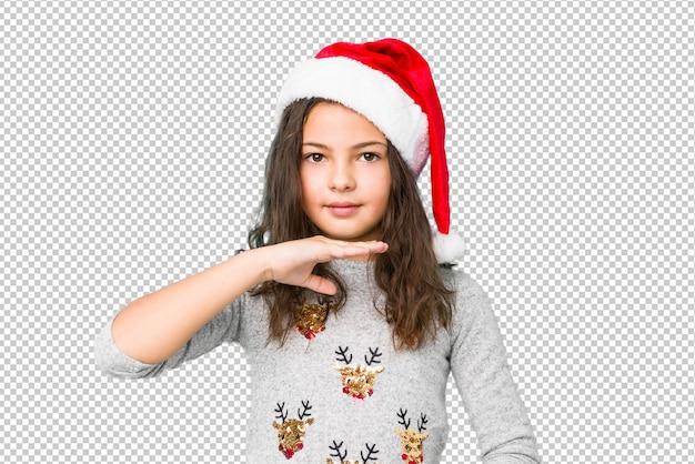 Kleines mädchen, welches den weihnachtstag hält etwas mit beiden händen, produktdarstellung feiert.