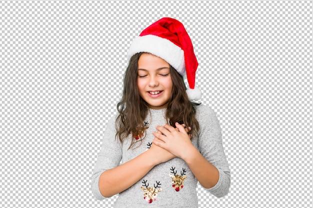 Kleines mädchen, welches den weihnachtstag lacht feiert, hände auf herzen, konzept des glückes halten.