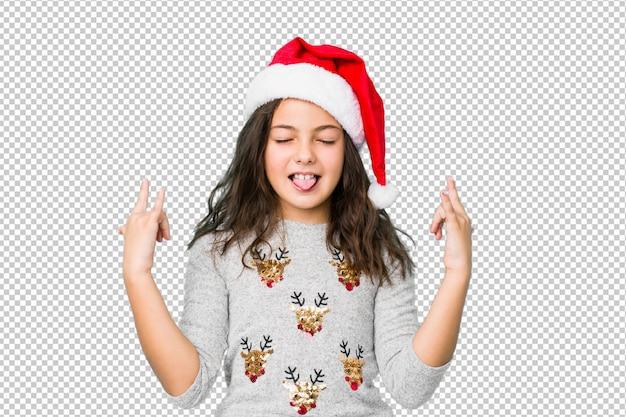 Kleines mädchen, welches den weihnachtstag zeigt felsengeste mit den fingern feiert