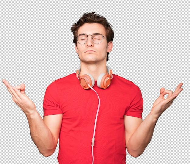 Konzentrierter junger mann, der eine geste des meditierens macht