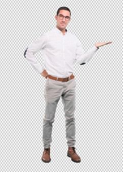 Konzept eines jungen mannes, der etwas mit seinen händen - voller körperschuß zeigt
