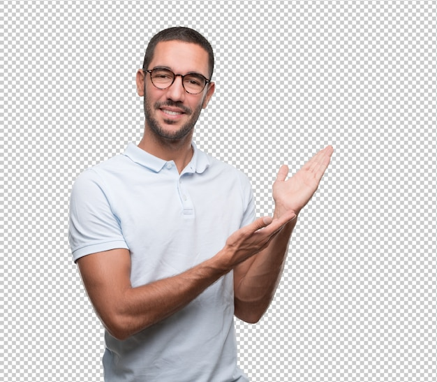 Konzept eines überzeugten jungen mannes, der etwas mit seinen händen zeigt