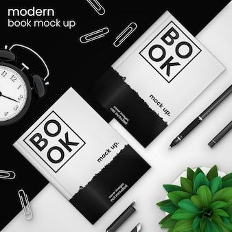 Kreative, moderne bucheinband-modellschablone von zwei büchern auf schwarzem mit wecker, büroklammern, stift und grünpflanze, psd-spott oben