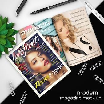 Kreative, moderne zeitschriftenmodellschablone von zeitschrift zwei auf modernem schwarzweiss-design mit büroklammern, stift und grünpflanze, psd verspotten oben