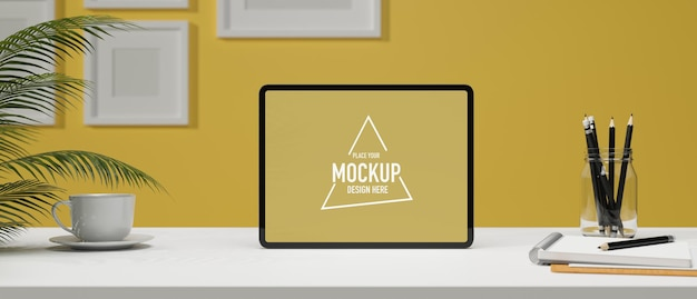 Kreativer arbeitsbereich in gelber wand leerer tablet-bildschirm auf weißem tisch und leerer rahmen an der wand