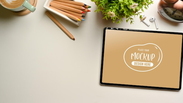 Kreativer flacher arbeitsbereich mit digitalem tablet-modell, buntstiften und dekorationen, draufsicht