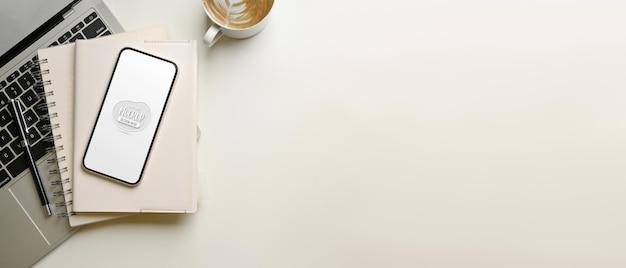 Kreativer flacher arbeitsbereich mit smartphone-modell, laptop und kaffeetasse, draufsicht