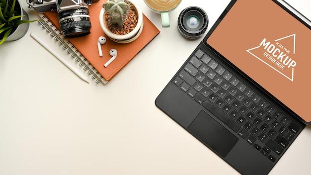 Kreativer flat-lay-arbeitsbereich mit digitalem tablet-modell, kamera, notebook und kopierbereich auf weißem schreibtisch, draufsicht