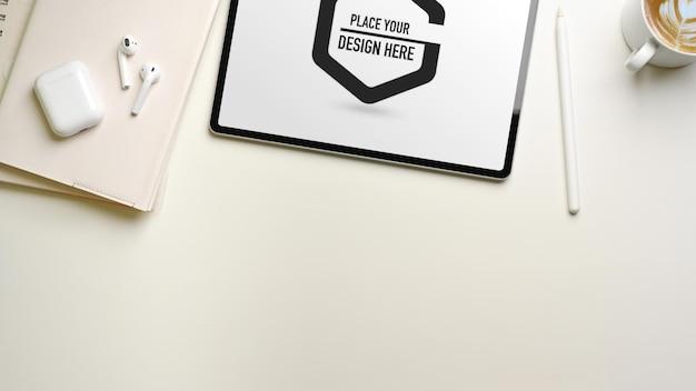 Kreativer flat-lay-arbeitsbereich mit digitalem tablet-modell, notebooks und zubehör, draufsicht