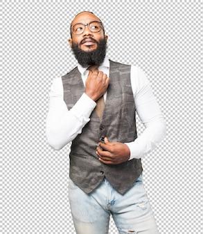 Kühler schwarzer mann, der seine krawatte justiert