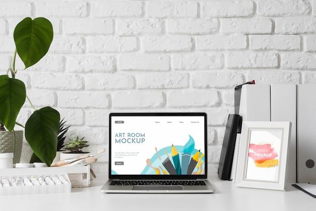 Künstlerarbeitsplatzschreibtisch mit werkzeugen und laptop