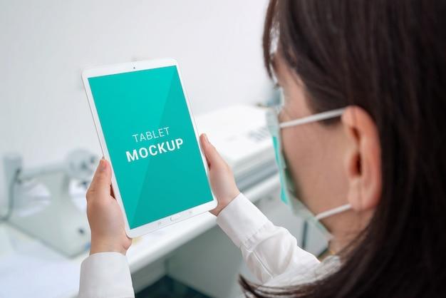 Labortablettenmodell. konzept der koronavirusforschung. wissenschaftler mit maske, die tablette ih krankenhaus hält