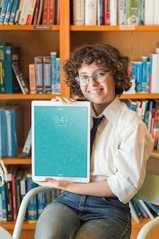 Lächelnde frau, die tablettenmodell in der bibliothek hält