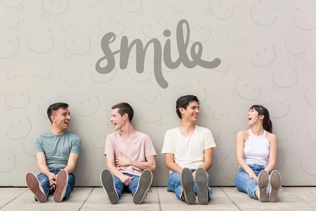 Lächelnde freunde posieren auf dem boden