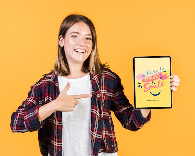 Lächelnde junge frau, die finger auf ein tablettenmodell zeigt