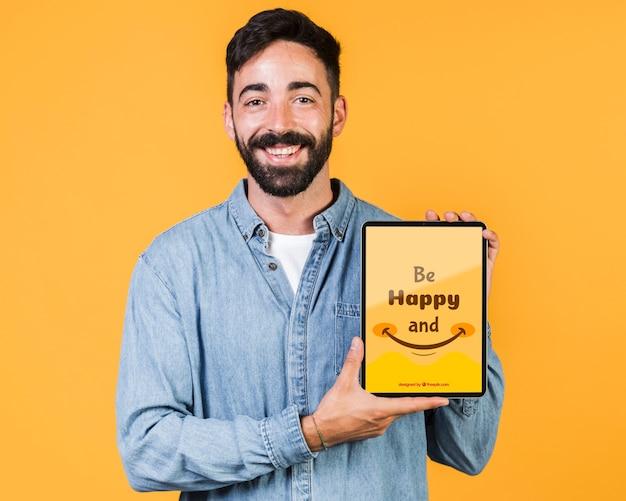 Lächelnder junger mann, der tablettenspott hochhält
