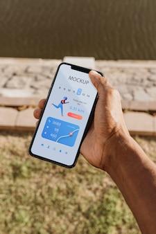 Läufer hält ein modell-smartphone