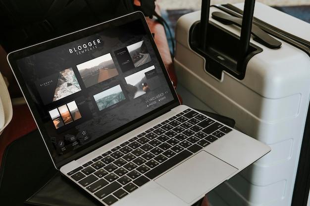 Laptop neben einem gepäck im flughafen