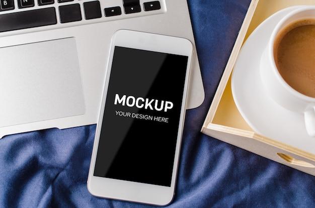 Laptop und smartphone, kaffeetasse und notebook auf dem bett in der morgenzeit