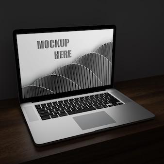 Laptopbildschirmmodell in der dunkelheit auf hölzernem schreibtisch