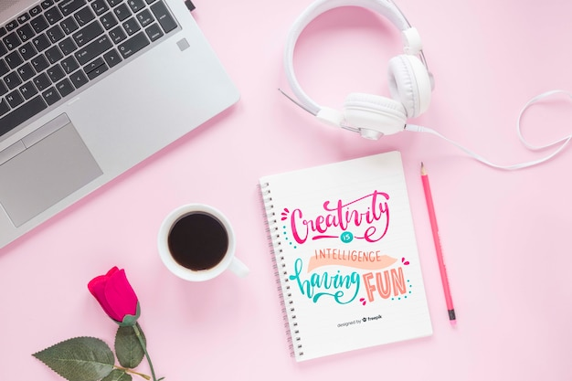 Laptopkopfhörer und -notizbuch auf rosa hintergrund